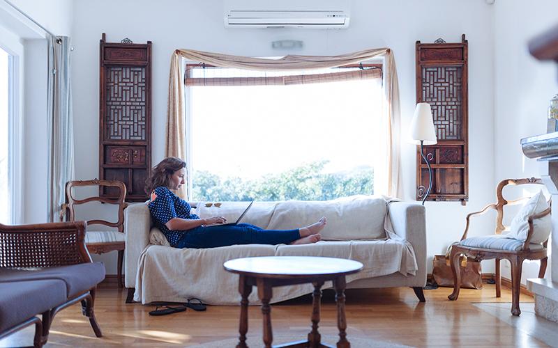 ソファでくつろぎながら仕事をする女性