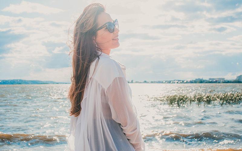 海辺で紫外線を浴びる女性