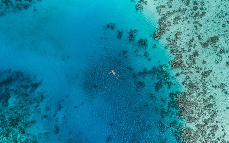 サンゴ礁の海に浮かぶ女性